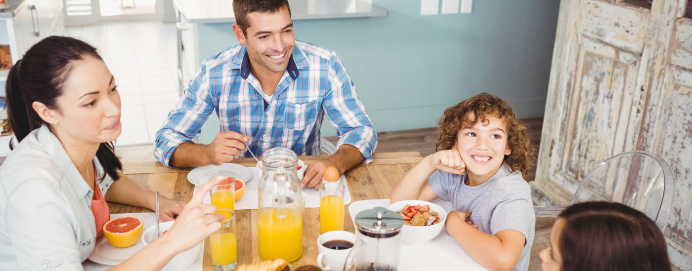 photodune-15254404-high-angle-view-of-happy-family-eating-breakfast-at-table-in-house-m-e1465504173487